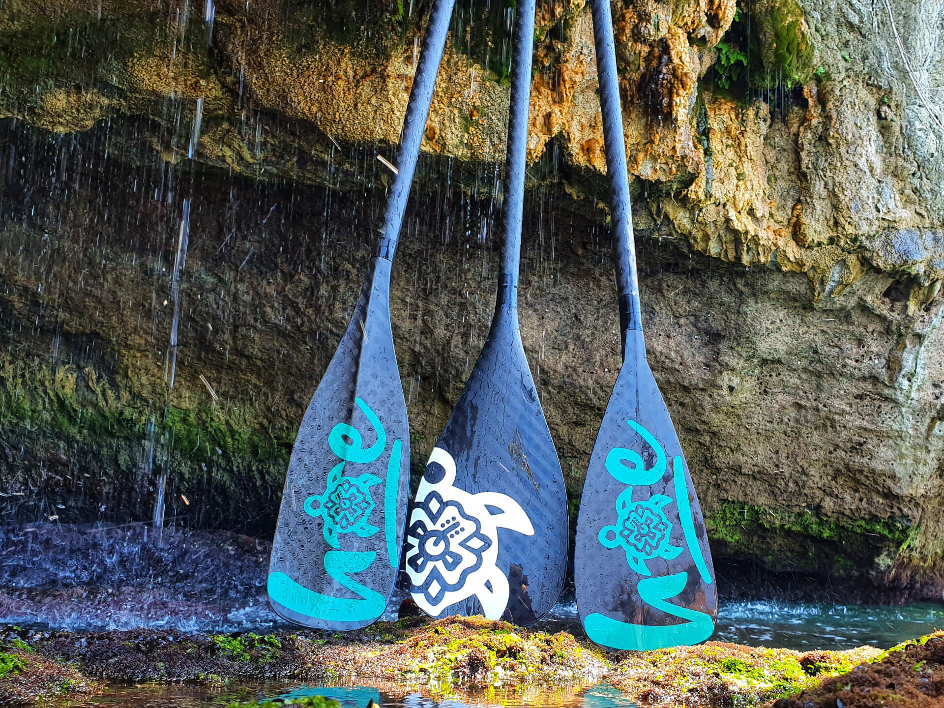 3 hoe custom paddles on a rock under a waterfall